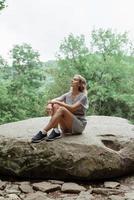 vrouw zittend op een grote rots in het bos, rusten of mediteren foto