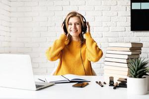 jonge lachende vrouw in zwarte koptelefoon die online studeert met behulp van laptop foto