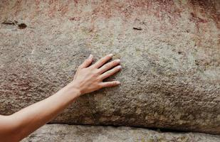 vrouwenhand die het rotsoppervlak aanraakt foto