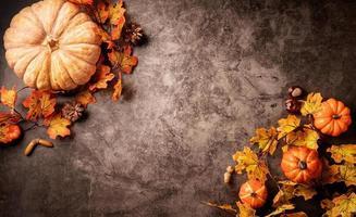 herfstdecoraties met pompoenen en bladeren bovenaanzicht op zwart foto