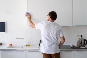 man die de keukenoppervlakken schoonmaakt foto
