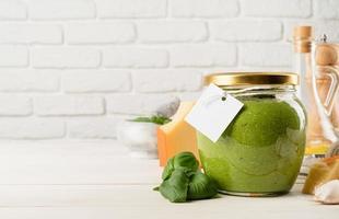zelfgemaakte pesto-saus in een glazen pot met een blanco tag, mock-upontwerp foto