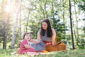 interraciale familie van moeder en dochter in het park met een picknick foto