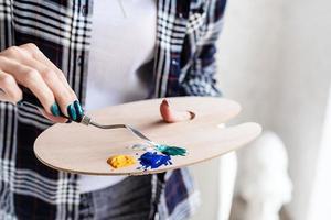 close-up van vrouwelijke kunstenaarshanden die kleuren mengen op houten kunstpalet foto