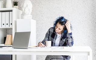 ontwerper aan het werk met kleurenpaletten en laptop in haar studio foto