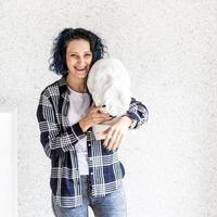 lachende vrouw kunstenaar in haar atelier met gips sculptuur foto