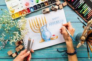 bovenaanzicht van vrouwelijke handen die een aquarelkunst tekenen gelukkige hanukkah foto