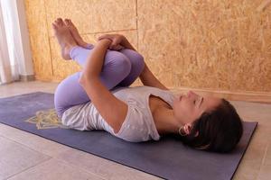 jonge vrouw die yoga beoefent, ontspannen in knieën tot borst pose foto
