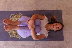 bovenaanzicht van sportief meisje dat thuis of in een yogastudio traint foto