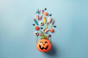 Halloween-snoepjes en snoepjes in een pompoenpot, bovenaanzicht op blauwe achtergrond foto