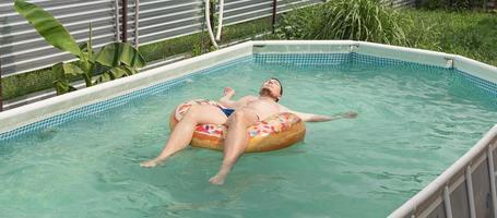 jonge man zonnebaden op opblaasbare zwembuis in het zwembad foto