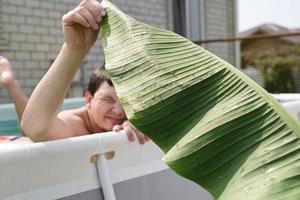 jonge man zwemmen in het zwembad, met een palmblad foto