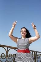mooie jonge vrouw opende haar handen naar de blauwe lucht foto