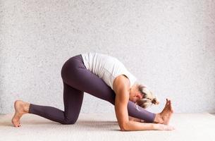 jonge aantrekkelijke vrouw die yoga beoefent, sportkleding draagt foto