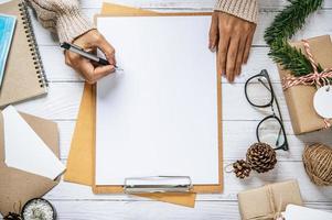 een hand die een pen vasthoudt om op een klembord te schrijven foto