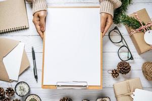 hand houdt klembord op een witte houten tafel foto
