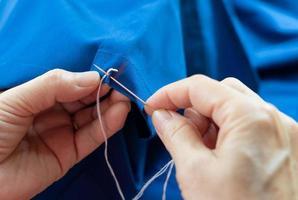vrouw die naald gebruikt om te naaien foto