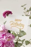 de gelukkige verjaardag met bloemencompositie foto