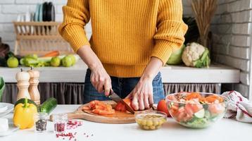 vrouwelijke handen maken salade snijden tomaten in de keuken foto