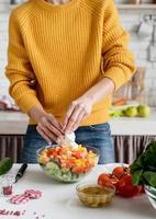 vrouwelijke handen maken salade snijden fetakaas in de keuken foto