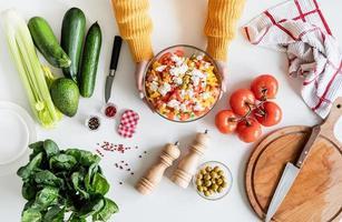 bovenaanzicht van vrouwelijke handen die Griekse salade maken foto