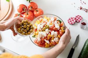 vrouwelijke handen die Griekse salade maken die olijven aan de kom toevoegen foto