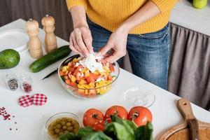 handen maken van salade snijden fetakaas in de keuken foto