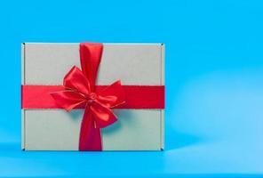 geschenkdoos met rood lint op blauwe achtergrond foto