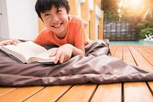 een jongen die lacht met een boek op houten tafel. thuis leren foto