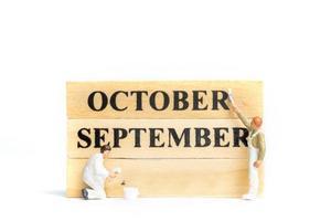 miniatuurmensen, arbeider die oktober op houten blok op witte achtergrond schilderen. foto