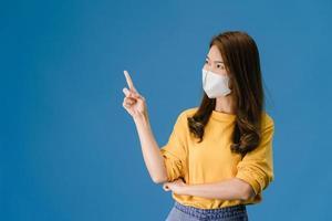 jong aziatisch meisje draagt gezichtsmasker toont iets op lege ruimte. foto