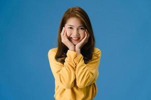 jonge Aziatische dame met positieve uitdrukking op blauwe achtergrond. foto