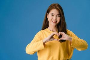 jonge azië dame toont handen gebaar in hartvorm op blauwe achtergrond. foto