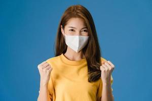 jong aziatisch meisje draagt gezichtsmasker dat vredesteken op blauwe achtergrond toont. foto