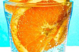 close-up van een schijfje sinaasappel met bubbels in een glas bruisend water foto