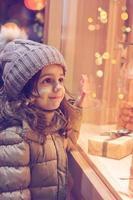 klein meisje voor de etalage van een winkel, vol ingepakte cadeaus foto