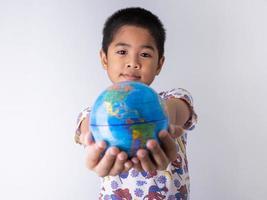 jongen die een wereldbol vasthoudt foto