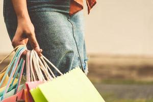close-up van een vrouw met een gekleurde papieren boodschappentas foto