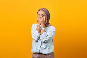 mooie Aziatische vrouw verborgen palmen gezicht kijk over haar fout foto