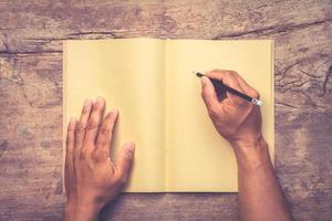 mannelijke hand met pen en schrijvend notitieboekje op oude houten tafel foto