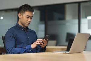 jonge aziatische zakenman die smartphone gebruikt terwijl hij op kantoor werkt. foto