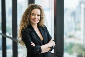 jonge mooie zakenvrouw staande armen gekruist foto
