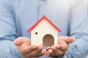 hand met mockup huis. verzekering onroerend goed lening foto