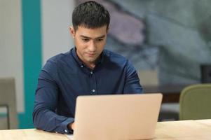 jonge aziatische zakenman die met laptop in bureau werkt. foto