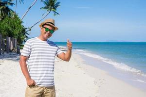 gelukkige jonge man op het tropische strand foto
