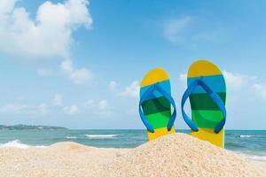 strandsandalen aan de zandkust. zomer concept foto