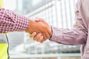 burgerlijk ingenieur handen schudden met zakenman foto