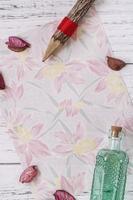 bloemenpapier met potlood en fles foto