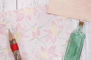 bloemenpapier met een potlood en een fles foto