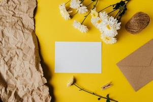 een blanco kaart met envelop en bloem wordt op een gele achtergrond geplaatst foto